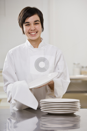 Smiling brunette drying dishes. stock photo, Smiling brunette woman drying dishes, smiling at camera. Vertical. by Jonathan Ross