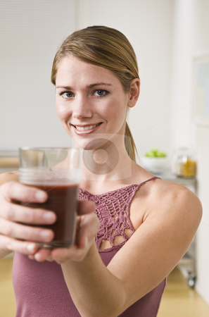 Blonde woman with smoothie. stock photo, Blonde woman showing smoothie to the camera, smiling at camera. Vertical by Jonathan Ross