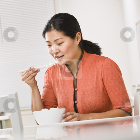 Asian woman eating rice. stock photo, Asian woman eating a bowl of rice with chopsticks. Square by Jonathan Ross