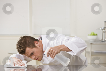 Attractive male cleaning table. stock photo, Attractive brunette male carefully cleaning table with cleaner. Horizontal. by Jonathan Ross