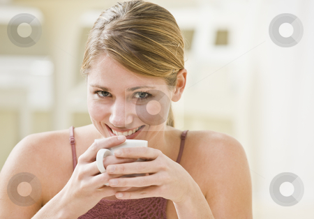 Woman Holding Mug stock photo, A woman is holding a mug and smiling at the camera.  Horizontally framed shot. by Jonathan Ross