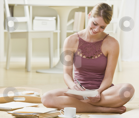 Woman Studying stock photo, A young woman is sitting on the floor and writing.  She is smiling and looking away from the camera.  Horizontally framed shot. by Jonathan Ross