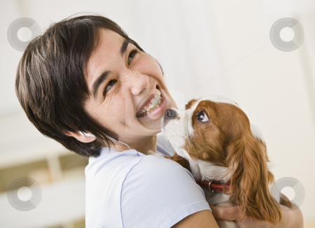 Woman Holding Dog stock photo, A woman is holding a puppy and smiling at the camera.  Horizontally framed shot. by Jonathan Ross