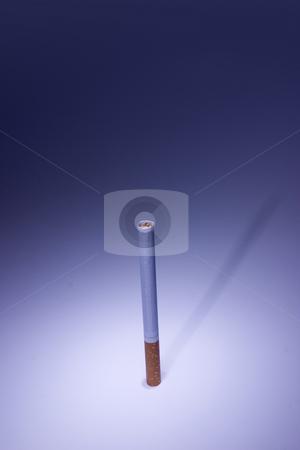 Isolated Cigarette Under Blue Light stock photo, Isolated Unsmoked Cigarette Under Blue Light by Mehmet Dilsiz