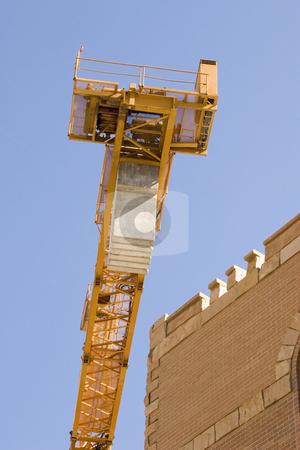 Construction Crane next to a Building stock photo, Construction Site Crane next to a Building by Mehmet Dilsiz
