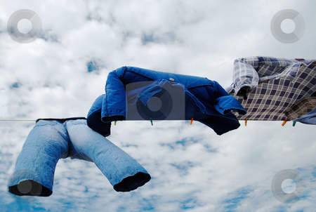 Trousers and shirts stock photo, Drying trousers and shirts on wind with copy space over cloudy sky background by Milsi Art