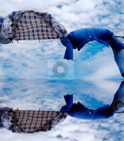 Shirts on wind stock photo, Drying shirts on wind with copy space on sky and water leaving for horizon background by Milsi Art