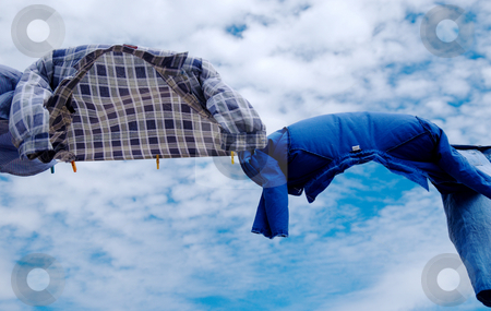 Shirts on wind stock photo, Drying shirts on wind with copy space on sky  background by Milsi Art