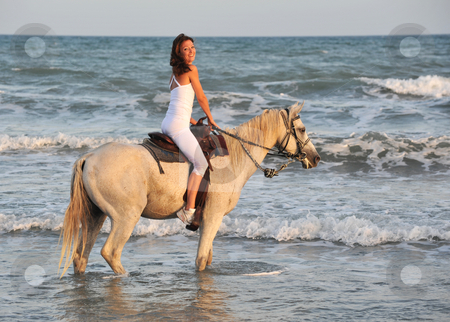 Riding woman in sea stock photo, Smiling riding young woman in the sea by Bonzami Emmanuelle