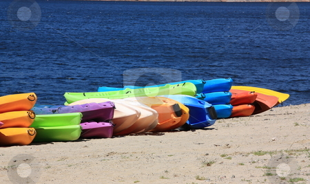 Colourful Kayaks stock photo, A row of colourful kayaks for hire lie on a beach with the blue water behind by Gozzoli