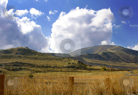 Country with Mountains stock photo, Country with Mountains and Cloudy Skies by Mehmet Dilsiz