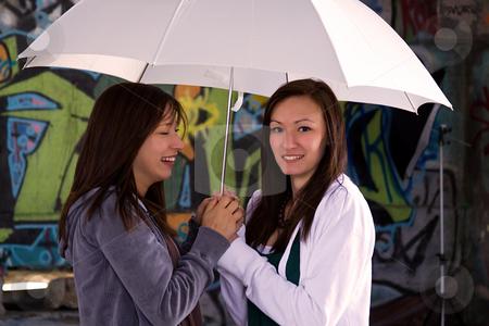 Teeangers Holding an Umbrella stock photo, Two Teengers Under an Umbrella by Mehmet Dilsiz