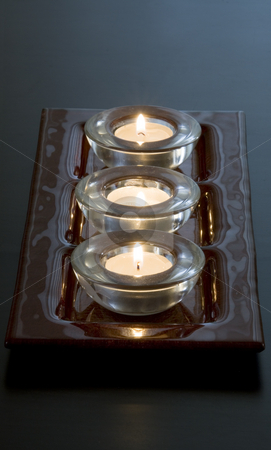 Candles in a Row stock photo, Three lit candles in a row by Mehmet Dilsiz