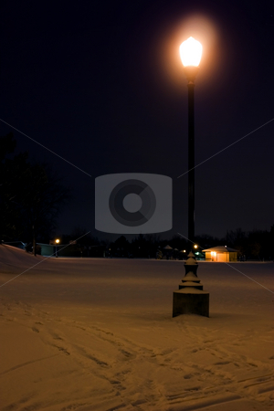 Park at night after a snow storm stock photo, Close up on a light post after a snow storm by Mehmet Dilsiz