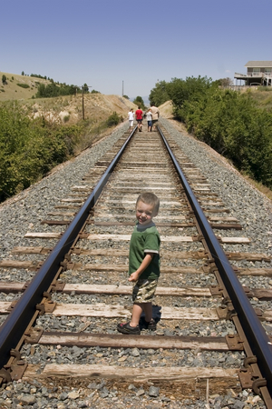 Little Boy on the Train Tracks stock photo, Little Boy Looking at the Camera on the Train Tracks by Mehmet Dilsiz