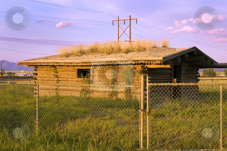Historic Old Pinoeer House Behind the Fences stock photo, Century Old Pinoeer House in Helena Montana with Grass Growing on the Roof by Mehmet Dilsiz