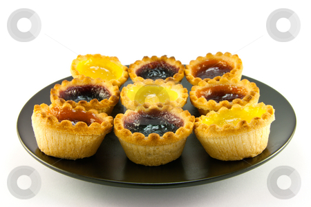Jam Tarts stock photo, Selection red and yellow small jam tarts on a black plate with  a white background by Keith Wilson