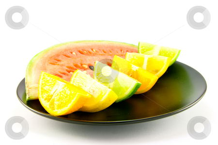 Watermelon with Citrus Wedges stock photo, Slice of juicy red watermelon with lemon, lime and orange wedges on a black plate with a white background by Keith Wilson