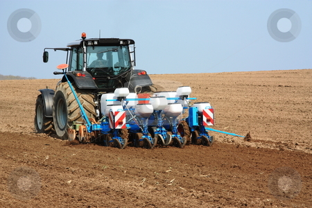 Planting the Spring Crop stock photo, An agricultural fine tilling and planting unit in use behind a tractor  to plant the spring crop. by Gozzoli
