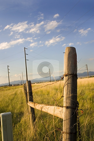 Wooden Gate with Electric Pole and Blue Skies on the Background stock photo, Wooden Fence and the Field with Electric Poles in Helena Montana by Mehmet Dilsiz