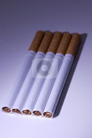 Isolated Cigarettes Under Blue Light stock photo, Isolated Unsmoked Cigarettes Under Blue Light by Mehmet Dilsiz
