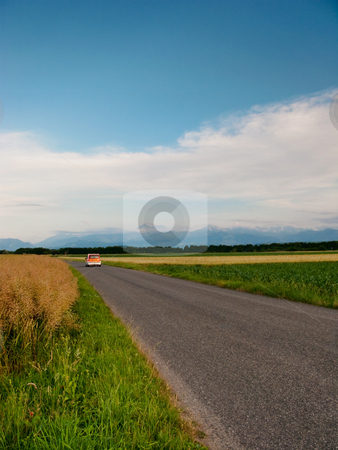 Scenic countryside road stock photo, Small orange car driving on a French countryside road by Laurent Dambies