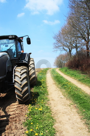 Lunchtime stock photo, A tractor stands in a newly ploughed field alongside a farm lane leading away from the camera, with yellow dandelions and a blue sky. by Gozzoli