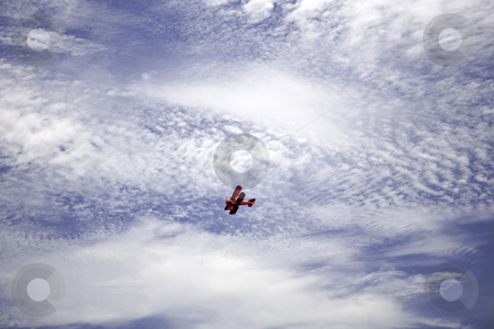 Red Biplane stock photo, Vintage red biplane flies beneath fair-weather clouds by Bart Everett