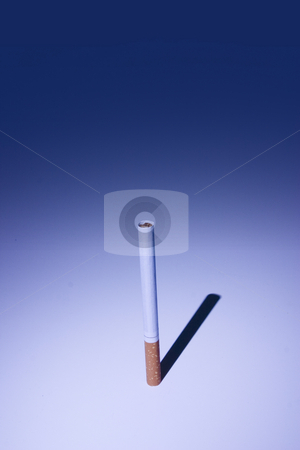 Isolated Cigarette Under Blue Light stock photo, Isolated Unsmoked Cigarette Under Blue Light by Mehmet Dilsiz