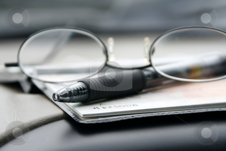 Paying the Bills with Check stock photo, Close up on the Glasses and the Checkbook by Mehmet Dilsiz