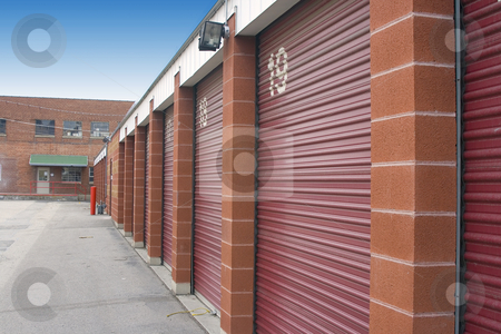 Mini Storage Unit Doors stock photo, Numbered Storage Unit Doors and its parking lot by Mehmet Dilsiz