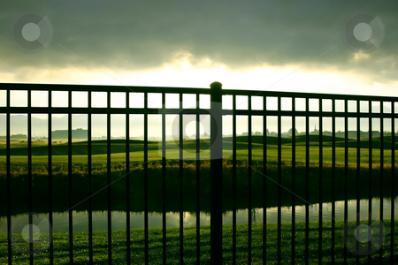 Sunrise Behind the Fence stock photo, Sunrise Behind the Fence, over the Golf Course by Mehmet Dilsiz