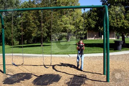 Little Boy Swinging stock photo, Mother swings the little boy by Mehmet Dilsiz