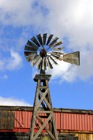 Old Wooden Windmill stock photo, Old Wooden Windmill with Clouds on teh Background by Mehmet Dilsiz