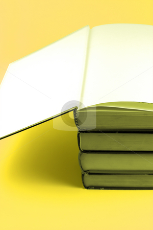 Books Stacked Up - Yellow Background stock photo, Books stacked up with the cover open on the top by Mehmet Dilsiz