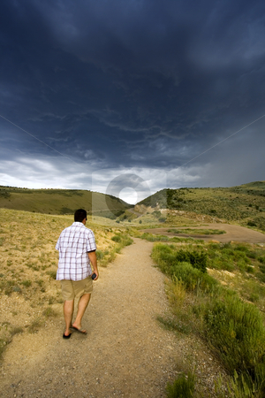 Walking into the Storm stock photo, Hiker walking in to the storm by Mehmet Dilsiz