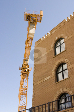 Construction Crane next to a Building stock photo, Construction Site Crane by Mehmet Dilsiz