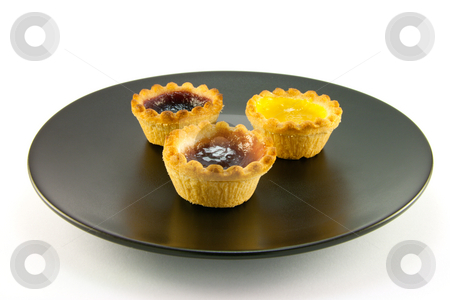 Three Jam Tarts on a Plate stock photo, Three red and yellow small pastry jam tarts on a black plate with a white background by Keith Wilson