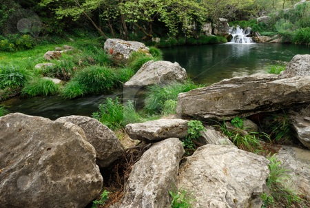Garden of Eden stock photo, Image shows a small lake with a waterfall in the background and rocks in the foreground by Andreas Karelias
