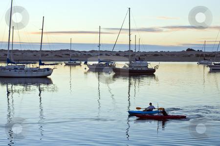 Morro Bay Marina Canoes stock photo, Two boys paddle canoes among boats in the Morro Bay marina after sunset by Bart Everett