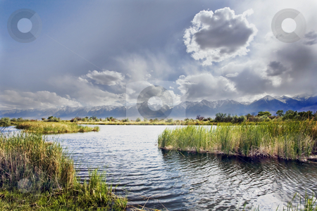 Sierra Nevada Storm stock photo, Clouds tumbling over the mountains cast a pall over a valley pond by Bart Everett