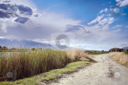 Billy Pond Road stock photo, Storm clouds tumble over the Sierras near a dirt road winding around a pond in the Owens Valley of California by Bart Everett