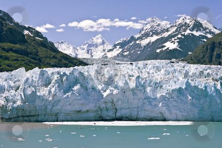 Wide Calving Glacier stock photo, Glacier sliding toward the ocean in Alaska's Glacier Bay colors the water with earth tones and ice debris as it calves into the sea. by Bart Everett