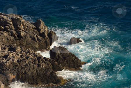 Rocks stock photo, Image shows a stormy sea hitting a rocky cosatline, photographed from above by Andreas Karelias