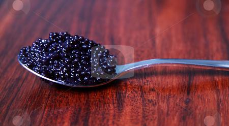 Caviar on a spoon stock photo, Black caviar on a spoon against a mahoney table by Daniel Kafer