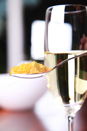 Caviar and champagne stock photo, Red caviar on a spoon next to a glass of champagne by Daniel Kafer