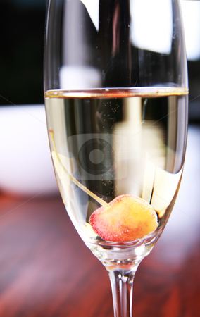 Glass of champagne with a cherry stock photo, Close-up of a champagne glass on a mahoney table with a cherry in the glass by Daniel Kafer