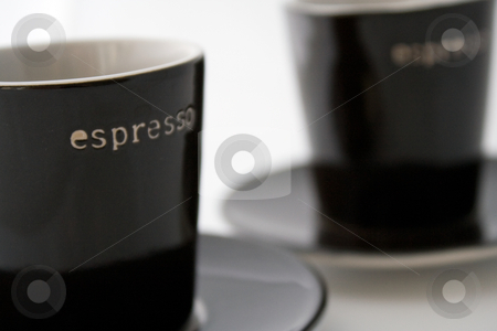 Two espresso cups stock photo, Two dark brown espresso cups and plates on a white background. by Natalia Banegas