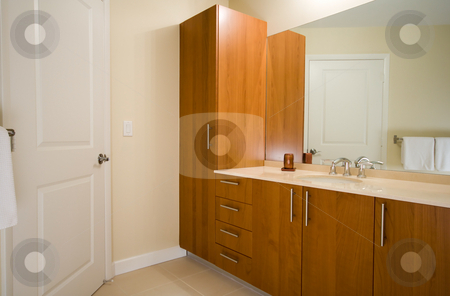 Bathroom interior stock photo, Interior of a new modern bathroom. Wooden cabinets, marble counter top, large mirror and chrome faucet. by Natalia Banegas