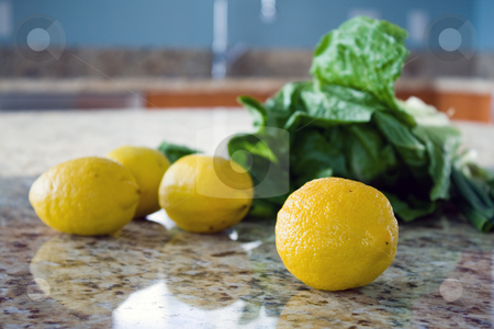 Lemons and salad leaves on a kitchen countertop stock photo, Lemons and salad leaves on a kitchen countertop. by Natalia Banegas